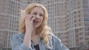 Close-up face of pretty smiling confident blond woman talking by cellphone in front of skyscraper. Urban lifestyle. Close-up face of a pretty smiling confident stock video footage