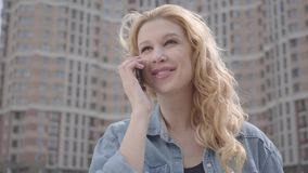 Close-up portrait of pretty smiling confident blond woman talking by cellphone in front of skyscraper. Urban lifestyle. Close-up face of a pretty smiling stock video