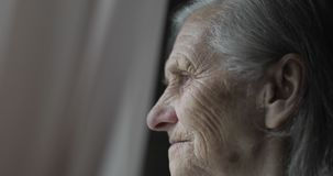 Close-up face of sad old woman with deep wrinkles.