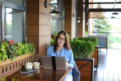 Lose up face of gladden customer browsing by laptop at resta. Close up face of satisfied customer browsing and enjoying social networks at restaurant  . Happy Stock Image