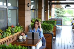 Lose up face of gladden customer browsing by laptop at resta. Close up face of satisfied customer browsing and enjoying social networks at restaurant  . Happy Royalty Free Stock Photography
