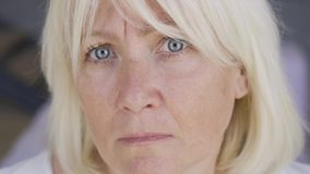 Close-up face of a scared frustrated mature woman looking at camera. The woman with blue eyes and blond hair at home stock footage