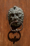Close-up of face-shaped knocker on wooden door in Aix-en-Provence. Stock Photos