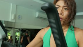 Young determined and athletic Asian Indonesian sport woman training fitness working hard at gym doing elliptical machine workout. Close up face shot of young stock video