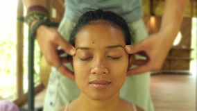 Close up face shotof young gorgeous and relaxed Asian Indonesian woman receiving traditional facial Thai massage with male hands. Working her head in wellness stock video
