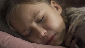 Close-up face of sick caucasian girl coughing while lying under blanket at home. The sad child has fever. Concept of. Close-up face of sick caucasian girl stock footage