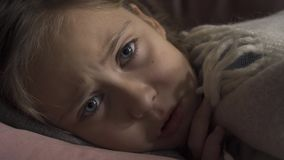 Close-up face of sick caucasian girl coughing while lying under blanket at home. The sad child has fever. Concept of. Close-up face of sick caucasian girl stock video