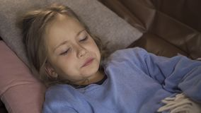 Close-up face of sick caucasian girl sneezing while lying under blanket at home. The sad child has fever. Concept of. Close-up face of sick caucasian girl stock video footage