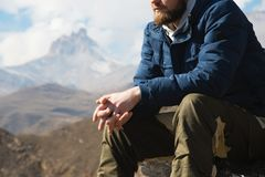 Close-up without a face sitting hipster on a stone high in the mountains against the background of epic rocks. The. Concept of relaxation in the mountains Stock Photo