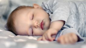 Close-up face of sleeping little cute infant child lying with closed eyes. Adorable lovely baby asleep enjoying serene dream resting on comfortable cot stock footage