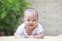 Close up face of smiling baby lying on soft bed at home terace u Stock Images