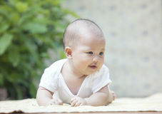 Close up face of smiling baby lying on soft bed at home terrace Stock Image