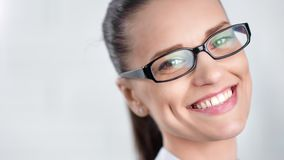Close-up face of smiling beautiful business woman wearing glasses isolated at white studio stock video