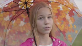 Close-up face of smiling caucasian blonde girl with light brown eyes dressed in pink jacket holding collorful umbrella. With painted yellow leaves. Pretty girl stock video footage