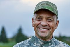 Close up face of a smiling mature soldier. Caucasian cheerful soldier outdoor royalty free stock photography