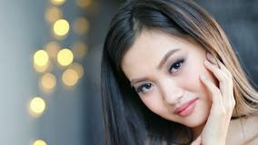 Close-up face of smiling modest Asian woman enjoying her pure young skin touching by hand. Portrait of adorable female looking at camera in background yellow