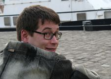Close-up of the face of a young man in glasses and a denim jacket stock photos