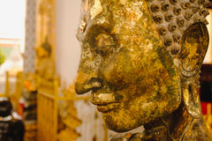 Close up face on starving Buddha head statue with lighting effect. Royalty Free Stock Photography
