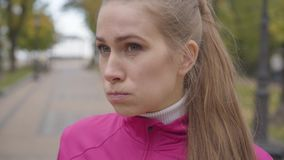 Close-up face of a tired Caucasian sportswoman with grey eyes drinking water and wiping her forehead. Confident female. Runner training in the autumn park in stock video footage