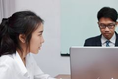 Close up face of unhappy Asian business woman having conflict with her colleague in office. stock photography