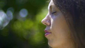 Close-up face of woman with closed-eyes, meditation in park, outdoor relaxation. Stock footage stock footage