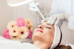 Close-up of the face of a woman relaxing during non-surgical fac. Elift treatment in a contemporary beauty salon with innovative technology royalty free stock image