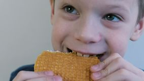 Close-up face of a 7years boy biting the waffles and chewing them. Crumbs fly in all directions. Close-up face of a seven-year-old boy biting the waffles and stock footage