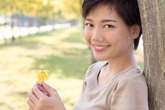 Close up face of young asian woman with smiling face and relaxin. G emotion standing in yellow blooming flowers park use for people healthy life and beauty Royalty Free Stock Images
