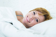 Close up face of young attractive woman with red hair lying in bed at home smiling happy looking healthy Stock Image