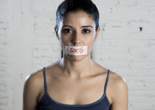 Close up face of young beautiful sad latin woman with mouth sealed on stick tape with the text no food Stock Photography