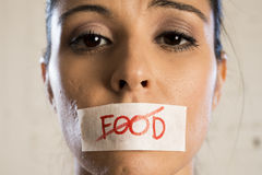 Close up face of young beautiful sad latin woman with mouth sealed on stick tape with the text no food Stock Images