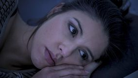 Young beautiful sad and worried latin woman suffering insomnia and sleeping disorder problem unable to sleep late at night lying o. Close up face of young Stock Photos