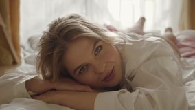 Close-up face of young charming woman lying on bed in the morning. Smiling Caucasian girl with pleasant smile looking at stock footage