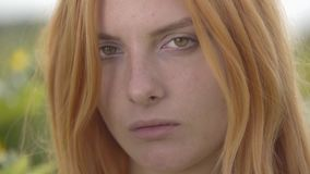 Close-up face of young confident girl with red hair and green eyes looking at the camera outdoors. Concept of beauty stock footage