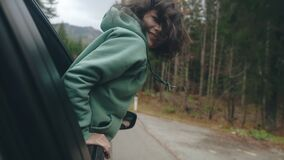 Close-up face of young girl traveling by car while road trip. Woman pulling her face and hands out of car window and
