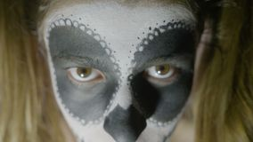 Close up face of young girl wearing halloween skull paint makeup and costume looking straight to camera -. Close up face of young girl wearing halloween skull stock video