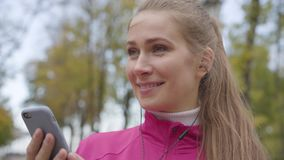 Close-up face of young grey-eyed Caucasian woman in pink sportswear turning on music in her headphones and starting. Running. Female runner training in the stock video