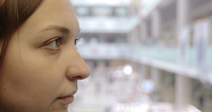 Close-up. The face of a young woman going down in the elevator. 4K Close-up. The face of a young woman going down in the elevator. Side view. Mall on the stock footage