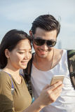 Close up face of younger asian man and woman looking to smart ph Royalty Free Stock Photography