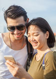 Close up face of younger asian man and woman looking to smart ph Stock Photos