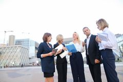 Close up faces of employees of business organization speaking ou. Members of business organization talking oute and smiling with document case and tablet in Stock Photography