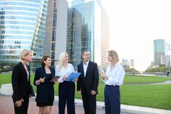 Close up faces of employees of business organization speaking ou. Members of business organization talking outside and smiling with document case and tablet in Stock Images