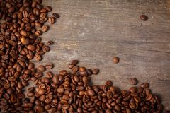 Coffee beans on dirty wooden desk. Close up of fair trade coffee beans on old wooden desk stock images