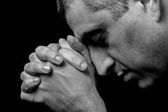 Close up of faithful mature man praying, hands folded in worship to god. With head down and eyes closed in religious fervor. Black background. Concept for Stock Image