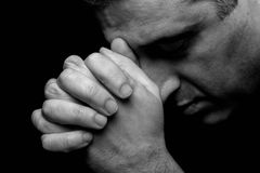 Close up of faithful mature man praying, hands folded in worship to god. With head down and eyes closed in religious fervor. Black background. Concept for Stock Photography