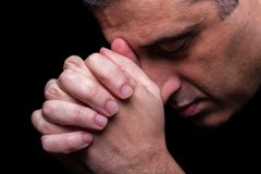 Close up of faithful mature man praying, hands folded in worship to god. With head down and eyes closed in religious fervor. Black background. Concept for Royalty Free Stock Photo