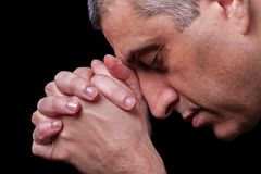 Close up of faithful mature man praying, hands folded in worship to god. With head down and eyes closed in religious fervor. Black background. Concept for Stock Photos