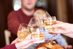 Close-up family clinking glasses on Thanksgiving on a table background. Cheers with champagne. Celebration concept. royalty free stock image