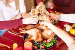 Close-up family clinking glasses on Thanksgiving on a table background. Cheers with champagne. Celebration concept. Stock Image