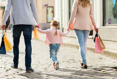 Close up of family with child shopping in city. Sale, consumerism and people concept - close up of happy family with little child and shopping bags in city royalty free stock photography